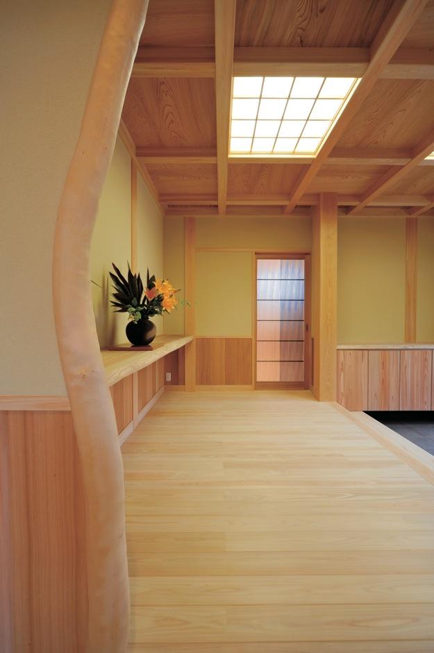 自然が生み出す変木の魅力を取り入れ玄関のアクセントに。腰板は秋田杉を使用