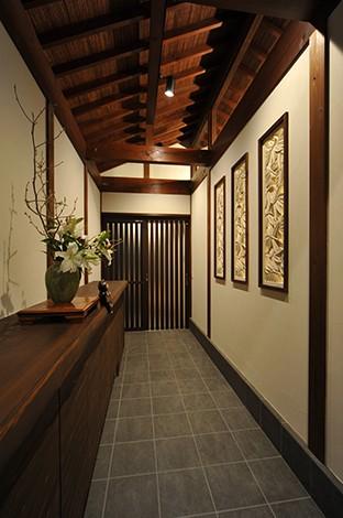 カネタケ竹内建築【デザイン住宅、自然素材、高級住宅】奥行き4mを超える土間が広がり、壁に飾られているのは『カネタケ』オリジナルの3連石のレリーフ。日がくれると柔らかな灯りが玄関を優しく包みこむ