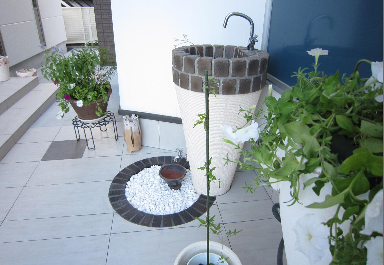 玄関外のアプローチ部分にもリゾートを求め、様々な植物やおしゃれアイテムを揃えている素敵な空間に