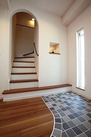 アイ・ディー・スリー 池田建設【屋上バルコニー、ガレージ、鉄骨鉄筋コンクリート構造】完全バリアフリーの玄関。たたき部分はモザイクタイルで。玄関収納と階段へのアプローチは塗り壁のアーチに