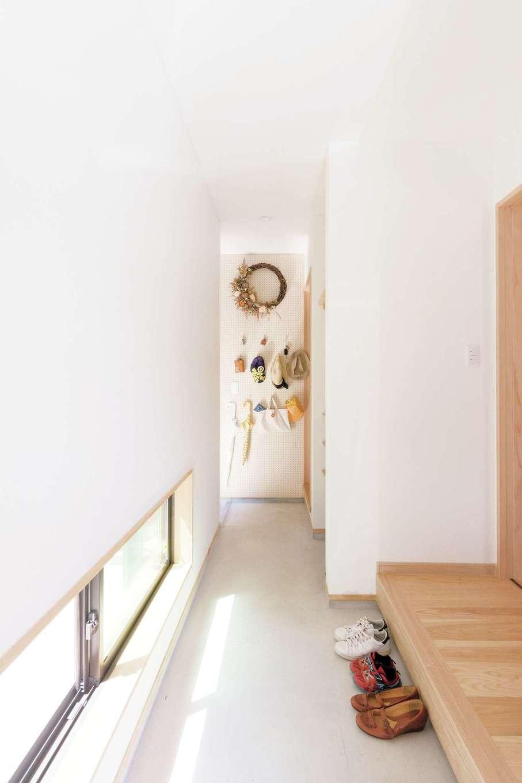 明かり取りの窓からの光が気持ちいい玄関。正面の壁は有孔ボード。外出時に必要なアイテムを掛けて収納できる