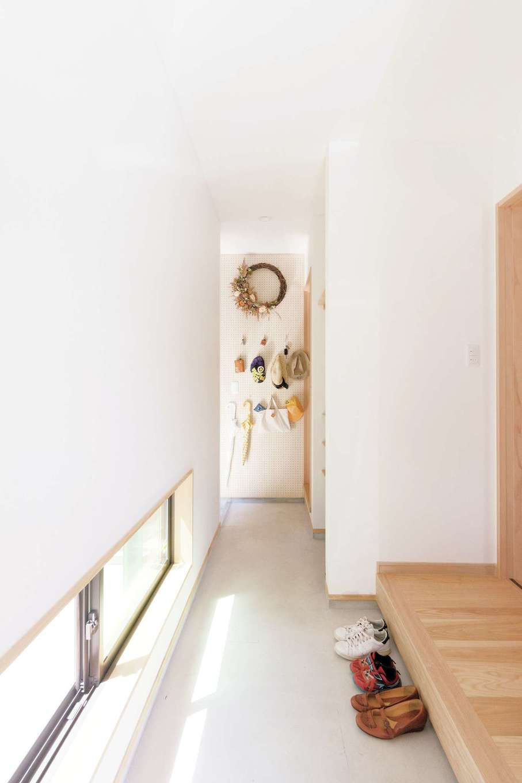 R+house三島(鈴木工務店)【子育て、二世帯住宅、趣味】明かり取りの窓からの光が気持ちいい玄関。正面の壁は有孔ボード。外出時に必要なアイテムを掛けて収納できる