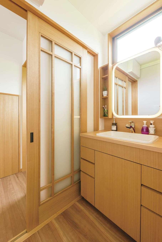 洗面台、建具、奥に見える階段下収納の扉。すべてをタモ材で造作