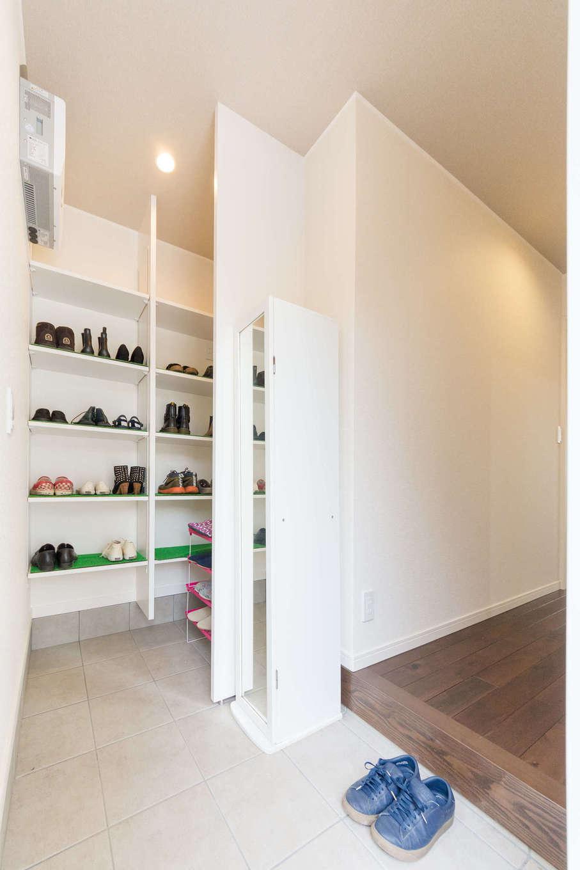 収納力抜群のシューズクロークのある玄関。敷き詰められた300角のタイルは、滑りづらく、手入れも簡単。高級感のある空間が、お客さまをお出迎えする