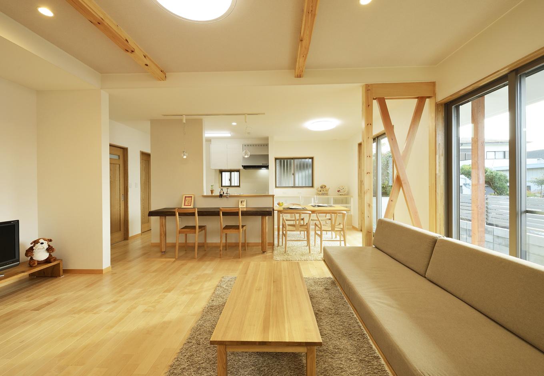 R+house三島(鈴木工務店)【デザイン住宅、収納力、自然素材】天井を高くとったリビング。カバ無垢の床や梁、柱のナチュラルな色合いがやさしい。 制作したドアなどの建具もこだわりの品だ