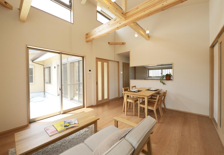 リビングから眺める中庭と勾配天井の高窓からは暖かな陽ざしと通風が適度にとれ、空調機のコスト削減にもつながっている