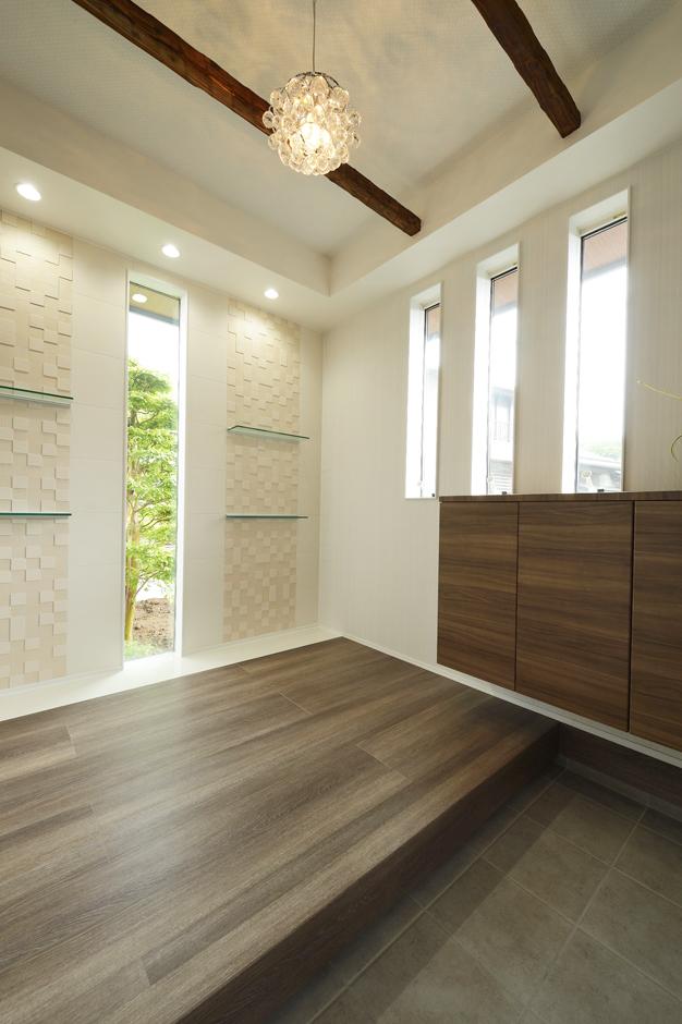 R+house三島(鈴木工務店)【デザイン住宅、和風、間取り】玄関正面の窓からは坪庭が臨め、絵画のように演出した。 壁のエコカラットは凹凸のあるものを選びエレガンスな雰囲気にし、 玄関の消臭効果にも役立っている