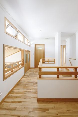 玄関の吹き抜けを覗く2階ホール。窓枠や階段手すりも無垢で統一されている。木材チップを使った壁紙「オガファーザー」は自然塗料で塗装し漆喰調の仕上がりに