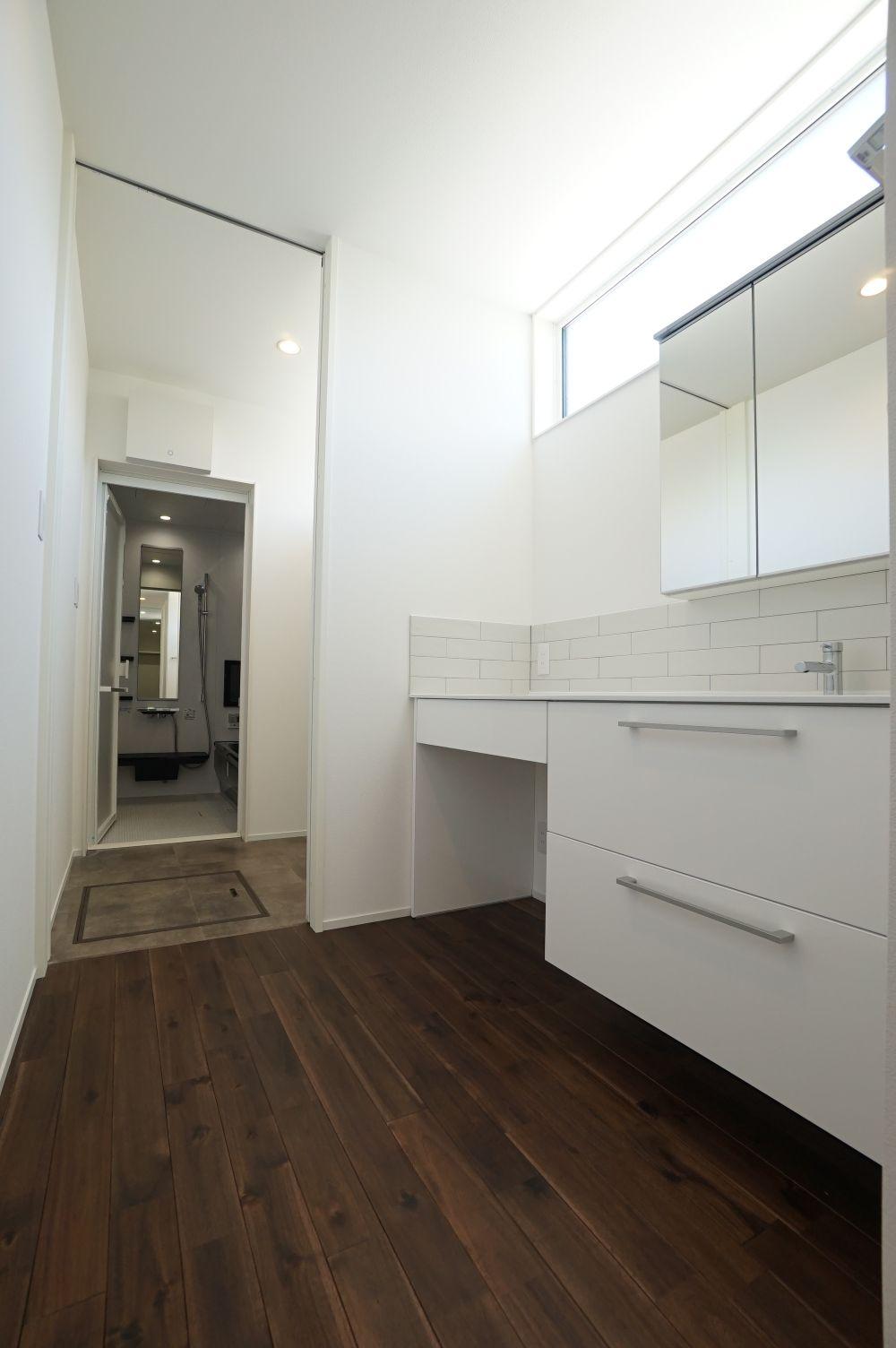 RIKYU (リキュー)【間取り、建築家、インテリア】ハイサイドライトから光が降り注ぎ、北面でも十分な明るさを確保した洗面脱衣室。ここから部屋干し兼家事室、ウォークインクローゼットまで一直線につながることで、奥さまの家事時間を大幅に短縮できる