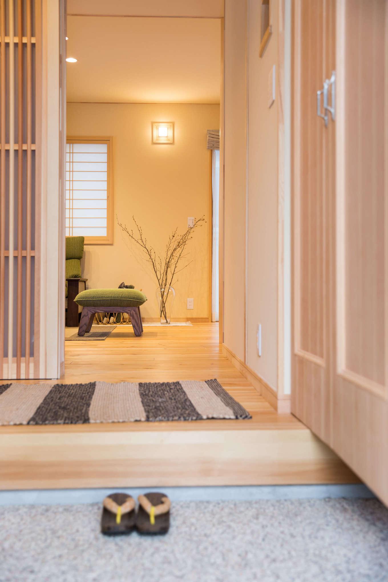 瀧口建設【1000万円台、デザイン住宅、子育て】玄関の戸を開けると、洗い出しの土間が迎えてくれる。奥様が選んだお香とヒノキの匂いが混ざり合い、心がホッと落ち着いていくのがわかる。床、壁、建具類はすべて、無垢材を使った人気の住宅ブランド「夢ハウス」仕様。木の優しい色合いが美しい