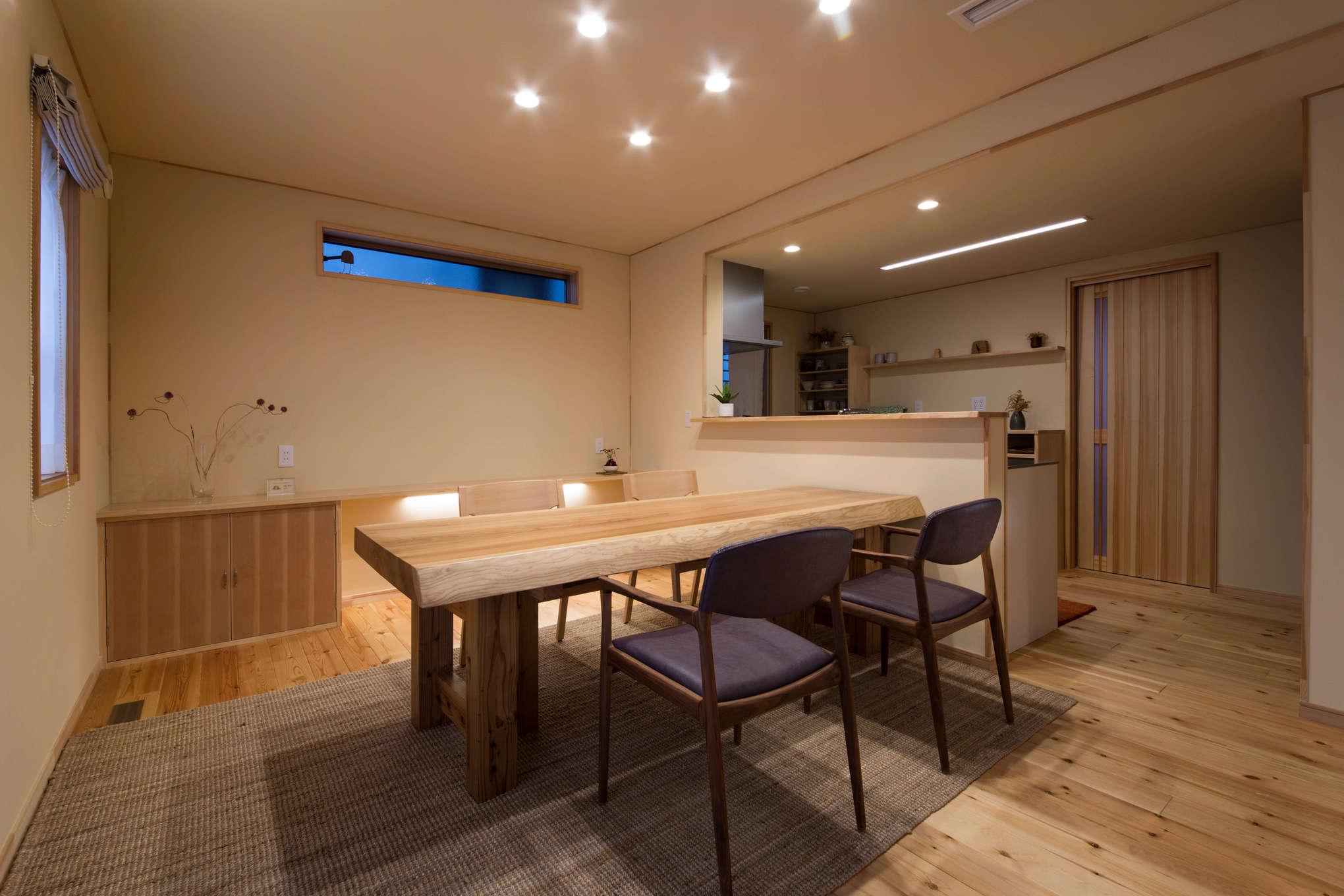 瀧口建設【1000万円台、デザイン住宅、子育て】杉一枚板を使ったダイニングテーブルは『瀧口建設』のオリジナル製作で、脚の高さを変えると座卓になる優れもの。「シュクレ浜松」で購入した無垢材の椅子も座り心地がよく、ここでワインを飲むのが夫妻の楽しみだ。カウンターやキッチン収納まで大工が造作した