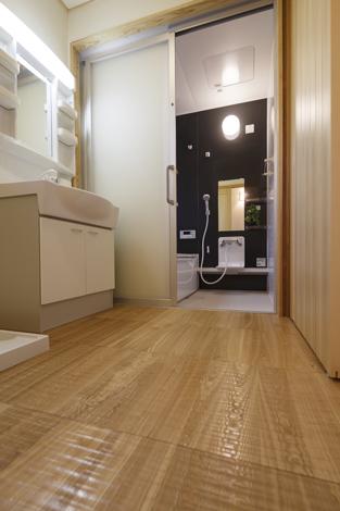 瀧口建設【和風、夫婦で暮らす、平屋】浴室は脱衣室との段差がないバリアフリー。タモ材のスプーンカット仕様の床は、歩いた時の当たりが柔らか