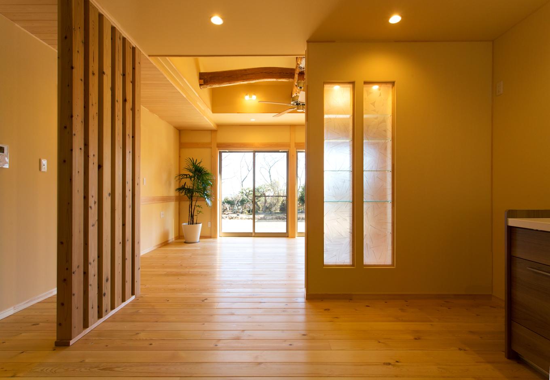 リビング北側のキッチンは通風と採光に工夫を。杉のつけ柱は玄関からの視線を遮り風は通してくれる。飾り棚の壁には透過性のあるパネルを使い、リビングから光を採りこんでいる