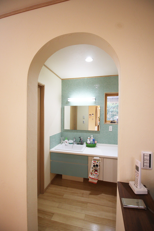 提坂工務店【趣味、自然素材、間取り】アールのかかった洗面入り口。壁にタイル、鏡は通常よりも大きなサイズを設置