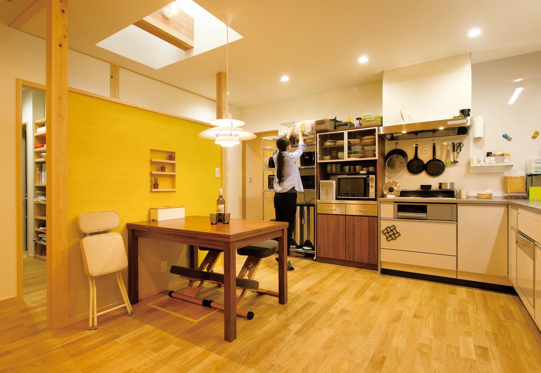 深見工務店 S-style【収納力、自然素材、平屋】キッチンをL字型にして空間を 広く。トップライトからダイニングテーブルに光がこぼれ落ち、気持ち良く朝食を囲む。ポールセンのペンダントライトがナチュラルな空間にぴったり