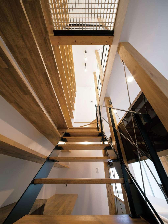 視線が抜けるストリップ階段。吹抜けにグレーチングを採用し、1階まで光を届ける。壁一面に大容量の本棚を造作し、ファミリーライブラリーとして活用