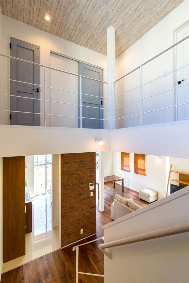 CKエンジニアリング【デザイン住宅、趣味、間取り】大きな吹き抜け、アイアンの手すり、淡いブルーのドアとタイル貼りのアクセントウォールのすべてが西海岸をイメージしている