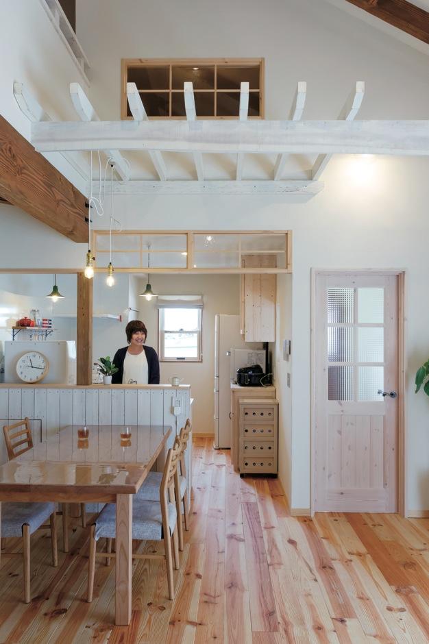 FAN CRAFT【収納力、自然素材、間取り】朝日を浴びながら料理できる明るいキッチン。1階はもちろん、吹抜けを通して2階の気配もわかる。白く塗ったパーゴラがダイニングキッチンのアクセントに。レトロな真鍮のランプソケットはアメリカLEVITON社製