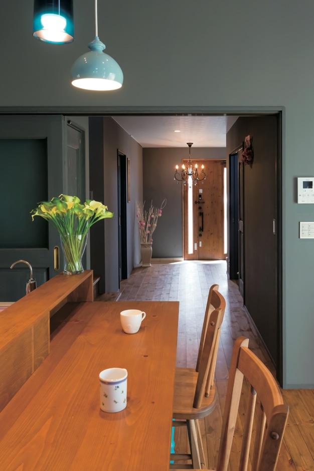 Takukenchiku【デザイン住宅、輸入住宅、インテリア】対面キッチンのカウンターごしに、広い廊下と玄関が見え る。グレーの壁を背景に、照明や花瓶の花の彩りが美しく映える。木製のカ ウンターやイスもオーダーメイド
