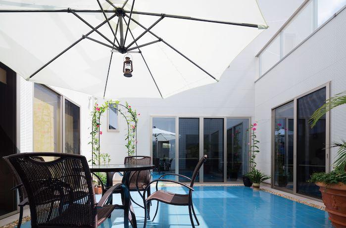 親世帯と子世帯をつなぐ中庭。青いタイルが水を張ったような錯覚を与え、リゾート感も倍増。大声を出しても空に抜けるので、近隣を気にせずBBQを楽しめる