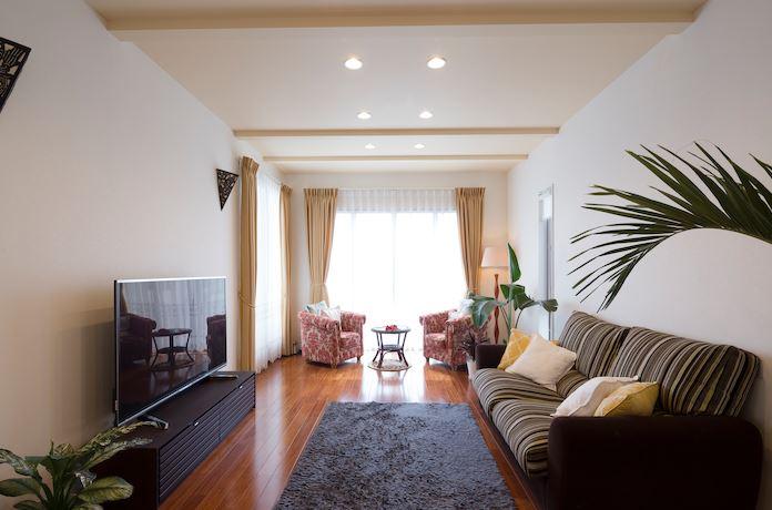 2階・子世帯のリビング。天井高3,000mmでより開放的な空間に。家具や照明、植栽までリゾートなテイストでコーディネートした。窓からバルコニーに出られ、中庭を見下ろせる