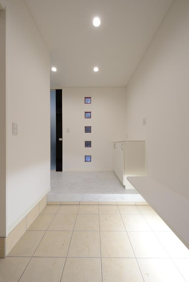Yamaguchi Design 【デザイン住宅、収納力、間取り】北側の玄関は、暗くならないよう色の入ったガラスブロックで明かりをとる。白で塗装した木のベンチは、ブーツや足袋を履くときに便利