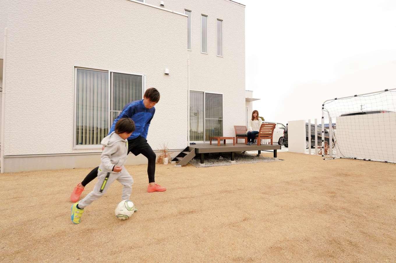 アイフルホーム 掛川店【デザイン住宅、子育て、間取り】高校サッカーで全国大会への出場経験のあるご主人が、息子さんにサッカーを教える。リビングに繋がるウッドデッキに屋外用ソファを備え、奥さまが見守る姿も