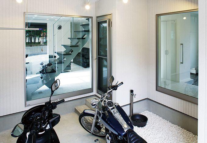 リビングと玄関ホールの両方から自慢の愛車を眺めることができる