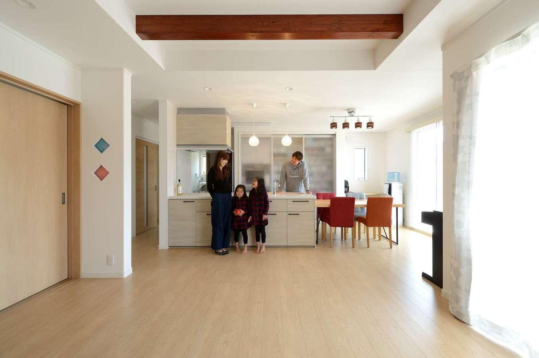 どこに行くにも必ずキッチンの前を通る間取りは、常に家族の繋がりを感じられる。リビングの天井を上げ、梁を見せることで空間にメリハリをつけた