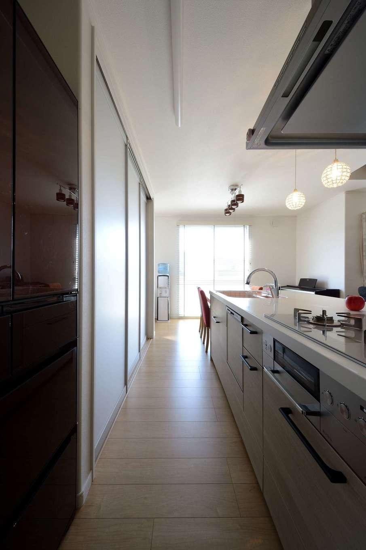 モデルハウスを見て採用した食器棚。半透明の引き戸で調理家電や食器を隠し、空間をすっきりと見せる。ダイニングテーブルをキッチンの横に配置したことで、配膳やお片づけの時間を短縮できる