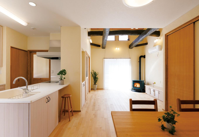 エコハウジング【収納力、自然素材、間取り】22畳のLDK。キッチンを中心にプランニングした間取りは、家族のコミュニケーションをとりやすい。右手に引戸を設けたことで、2階へ冷暖房効果が逃げるのを防いでいる