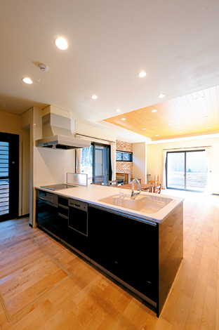 エコハウジング【収納力、省エネ】料理しながら家族の様子が見渡せる高級感ただようオープンキッチン。2面のウッドデッキで採光も十分
