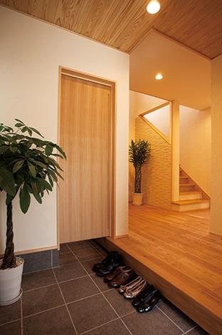 エコハウジング【デザイン住宅、自然素材、省エネ】玄関土間の奥はシューズクローク。床、天井、建具に天然木が使われ温かみあふれる空間が広がる
