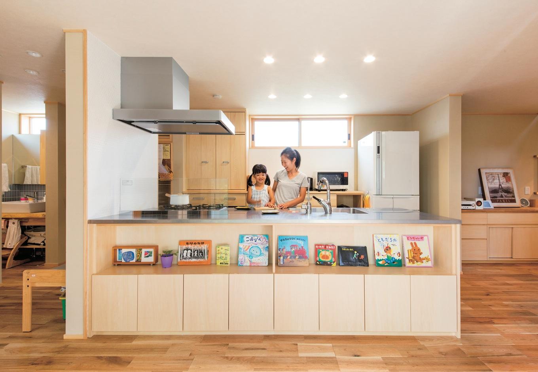 ぴたはうす 安食建設【子育て、省エネ、間取り】絵本を飾ったオーダーキッチンはホームライブラリーの機能も併せ持つ。土間、中庭、子どもの様子を眺めながら料理するのが奥さまの至福のひととき