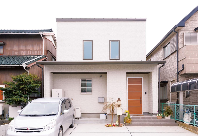 建築工房ハミング【子育て、自然素材、間取り】スタイリッシュな外観デザイン。ヤシの木は家族で植栽し、ポストはご主人の手作り。車を3台停めても玄関に入りやすいよう、ポーチを右側に長く伸ばした。ソーラーパネルを搭載するために、南面片流れの屋根を採用した