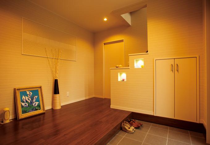 広々とした子世帯の玄関。壁には調湿・ニオイ吸着効果のあるエコカラットをデザイン配置。階段前の扉は親世帯へとつながる