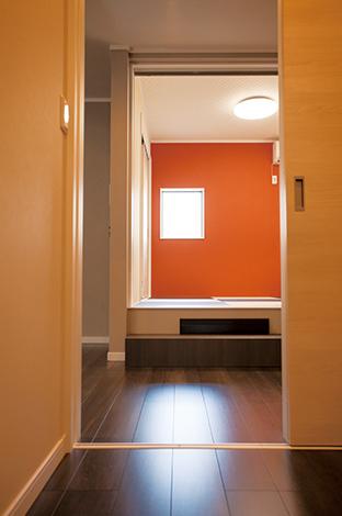 蔵一産業【1000万円台、子育て、収納力】小上がりの和室に配した、ビビッドなオレンジの壁紙がアクセント