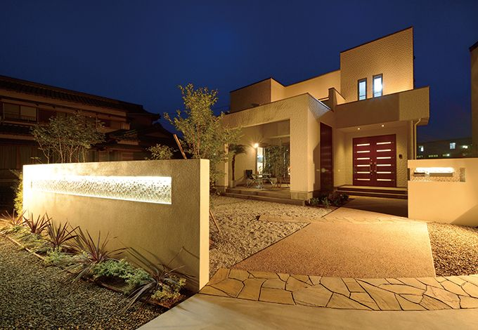 セイケンハウス【デザイン住宅、高級住宅、間取り】エッジの効いた外観は『セイケンハウス』の最も得意とするところ。緩やかなカーブを描いた塀のLED照明も独創的なセンスを主張している。アプローチに乱形の天然石を張り、高級感を演出した