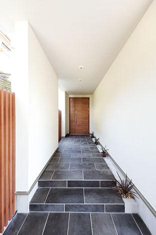 セイケンハウス【デザイン住宅、間取り、ガレージ】お洒落なレストランを彷彿とさせるエントランス。白い壁、茶色の格子、黒い床のバランス感覚がステキ