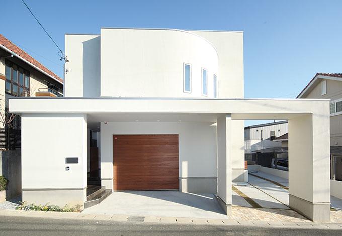 セイケンハウス【デザイン住宅、間取り、ガレージ】西日を避けるために窓を 少なくした外観。硬質な 直線と柔らかな曲線美の 融合は「セイケンハウス」 ならではのデザイン力