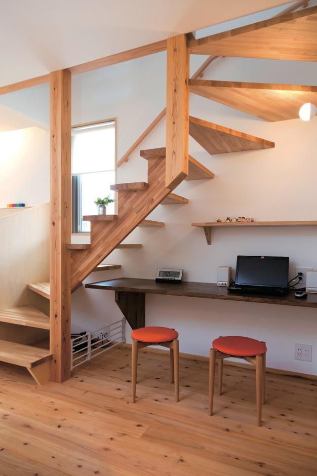 あだちの家。足立建築【狭小住宅、省エネ、間取り】木製のストリップ階段も部屋を広く見せる工夫のひとつ。 階段下には便利なパソコンコーナーを設けた