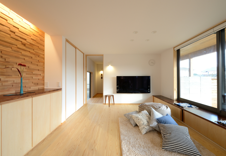 あだちの家。足立建築【収納力、省エネ、間取り】リビングは無節の床やウッドパネルのアクセントウォールで、ゲストを迎えるにふさわしいハレの空間を演出。大人数にも対応できるよう、窓際にベンチも設けてある