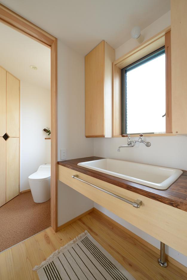 あだちの家。足立建築【収納力、省エネ、間取り】実用性を重視して、大きなシンクを採用した洗面台。窓につけた木の引き戸を閉め切ると大きな鏡が現れる