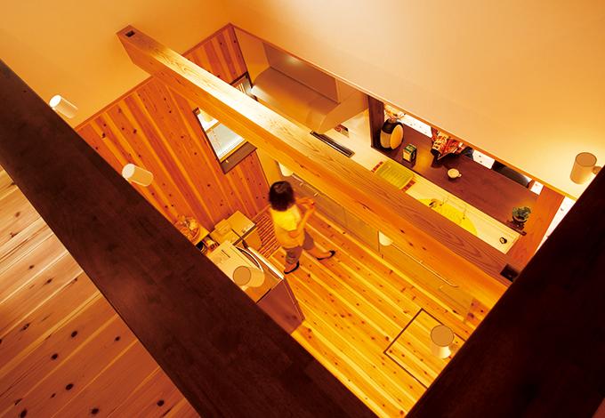 友和建設【趣味、自然素材、狭小住宅】2階ホールから1階のキッチンを見下ろす。天竜杉の太い梁を見る度に安心する