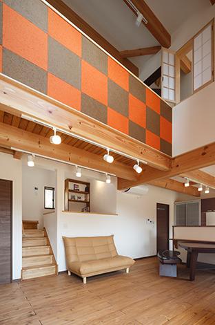 コバケンホーム(小林建設)【デザイン住宅、省エネ、間取り】開放感あふれる吹抜けのリビング。太い梁と床は国産赤松材を使用。2階ホールの壁に貼った市松模様の和紙が木の空間のアクセントになっている