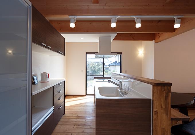コバケンホーム(小林建設)【デザイン住宅、省エネ、間取り】ご主人が手伝いやすいように、作業台を目一杯高くしたキッチン。ここから洗面脱衣所、浴室、サンルーム、ウッドデッキ、そしてキッチンへと回遊できる