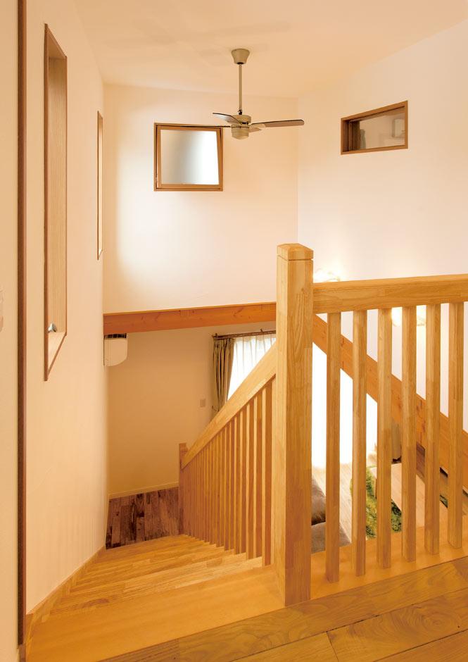 コバケンホーム(小林建設)【子育て、自然素材、間取り】無垢の格子の手すりが温かみを感じさせる階段。吹抜けの高窓が1階に明るさをもたらしている