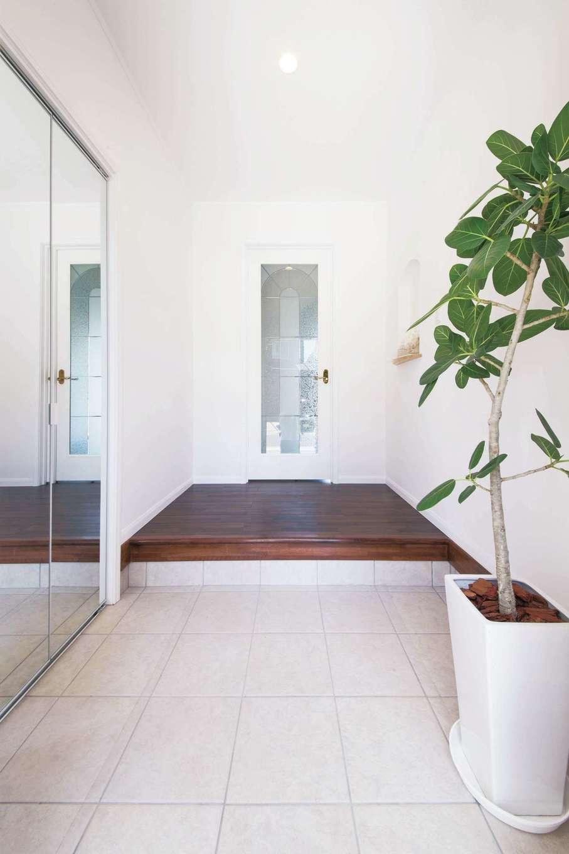セルコホーム浜松(オバタケイ)【輸入住宅、間取り、インテリア】白を基調とした玄関。サイドのミラー扉の奥はシューズクロークになっている