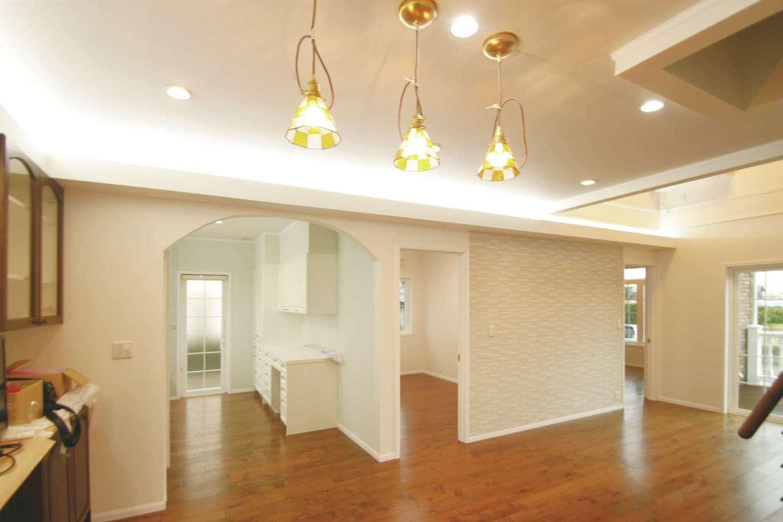 セルコホーム浜松(オバタケイ)【デザイン住宅、輸入住宅、平屋】LDKは吹き抜けと間接照明を用いて落ち着いた雰囲気に。ア-チ奥にはキッチンがあり、背面キャビネットで大容量の収納を確保