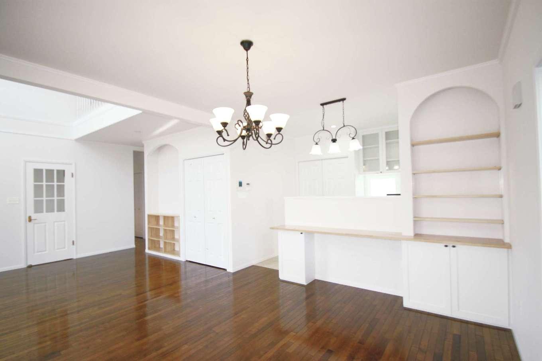 輸入フローリング、無垢の19㎜のオークカラーの床がホワイト基調の空間に映える。断熱性の高いオリジナル樹脂サッシは結露がない